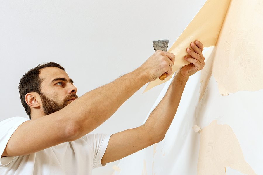 Man in with a scraper in the process of removing old wallpaper. Preparing the wall for sticking new wallpaper.